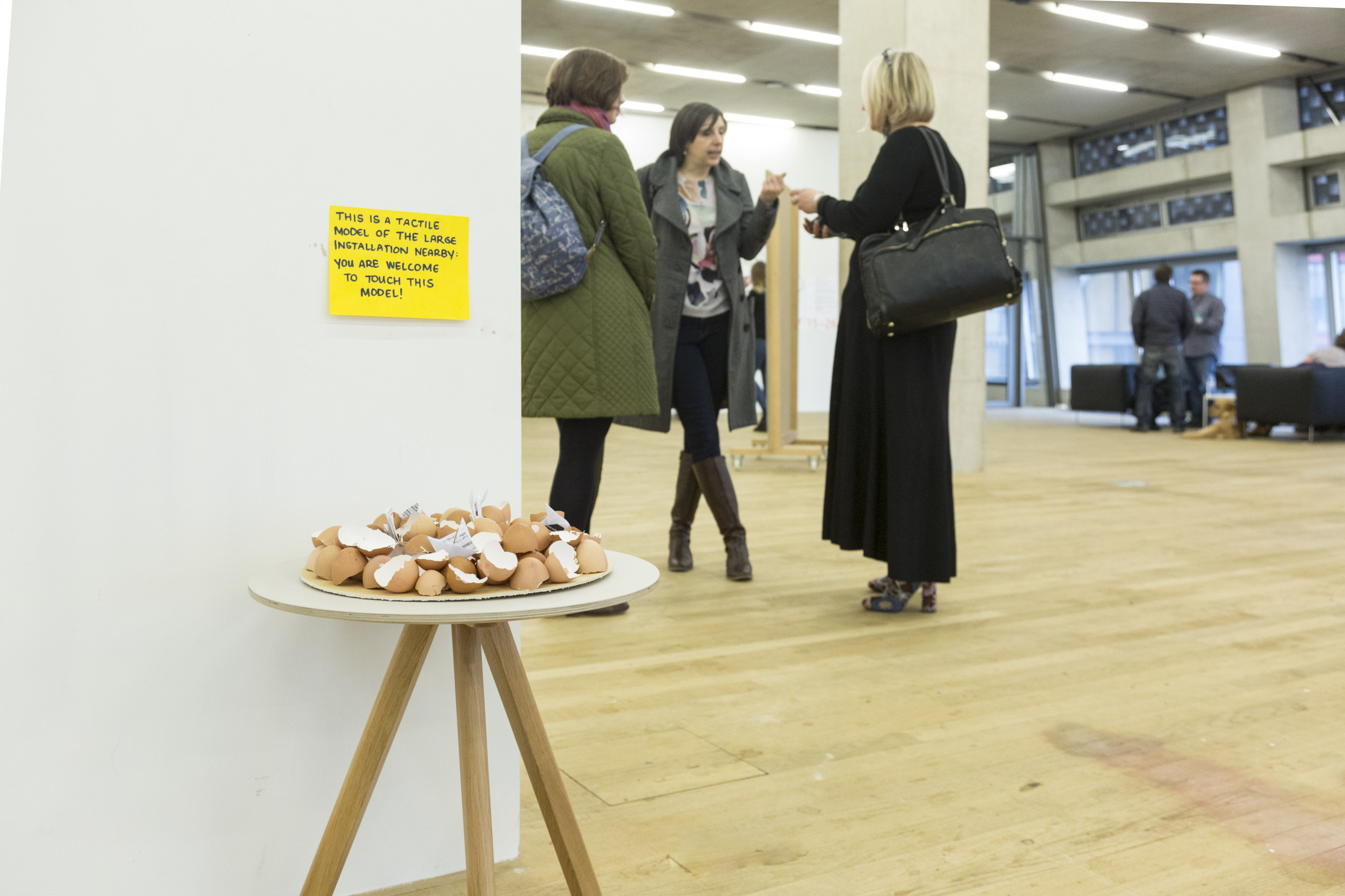 in the foreground, under a curatorial notice, a plate of eggshells acts as a model for touch exploring the larger eggshell installation it sits adjacent to, although the installation is out of the picture; in the background three woman are talking