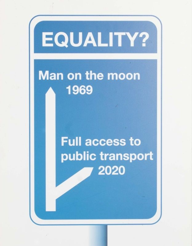Sign that reads: Equality? Man on the moon 1969, full access to public transport 2020.