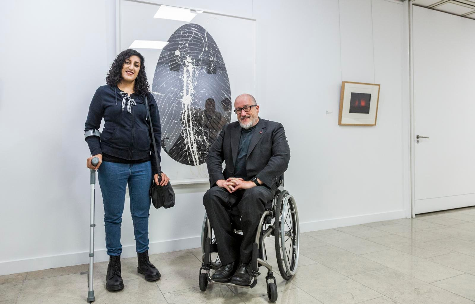 A white male wheelchair user and a young woman of South Asian heritage with a crutch are in a gallery space either side of a huge painting of a black oval on white canvas. They are looking at the camera and smiling