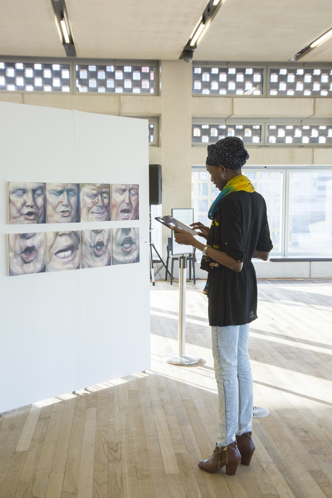 tall woman viewing small square paintings hung on white standing walls at tate exchange, artworks are of from the Shortlist 2017