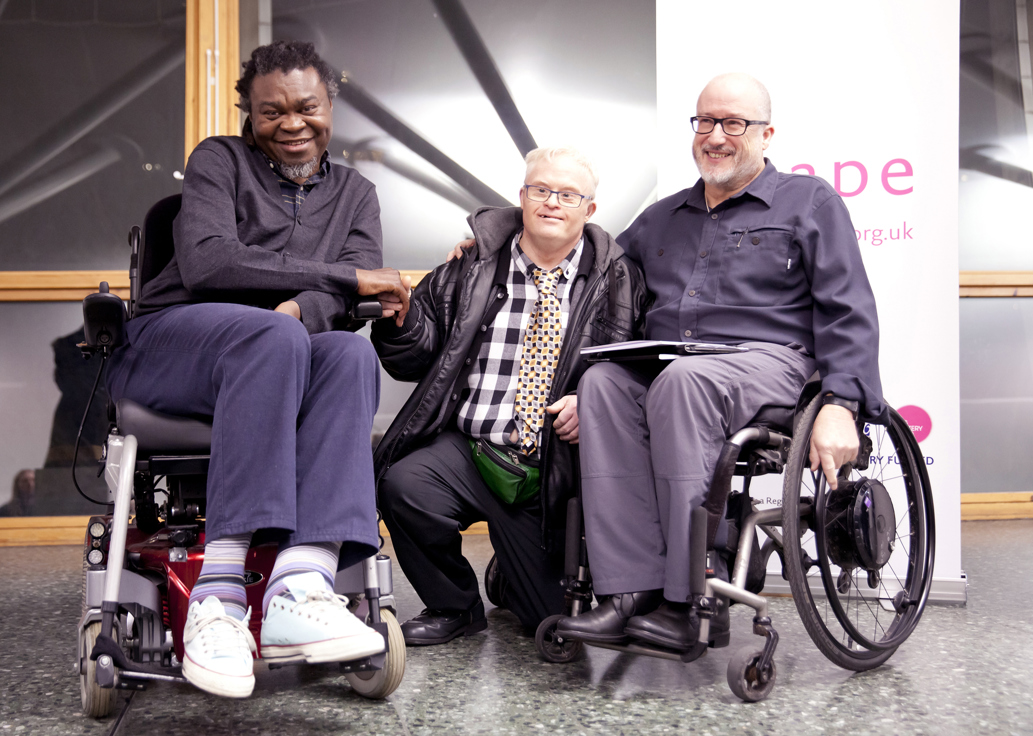 Yinka Shonibare, Richard Hunt and Tony Heaton in a row, smiling, in a gallery space