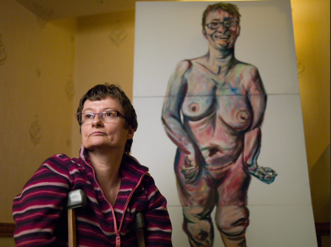 Artist Tanya Raabe in-front of her nude self-portait.