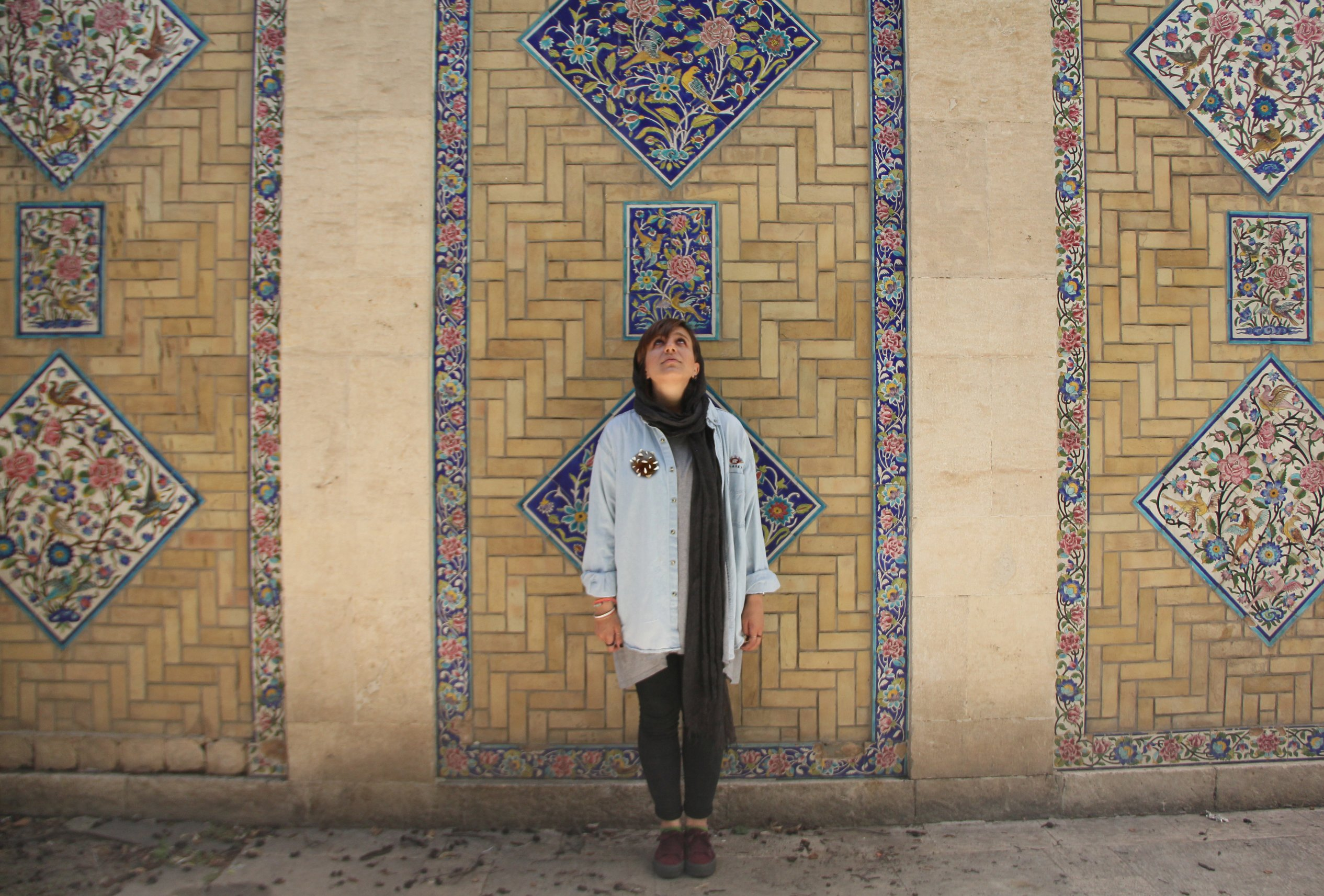 A woman stands in front of a beautiful tiled wall. Her head is bowed and she has the glimpse of a smile, She wears a moss green head scarf and yellow calf length jacket. On the jacket a large brown circular brooch is pinned at her right chest.