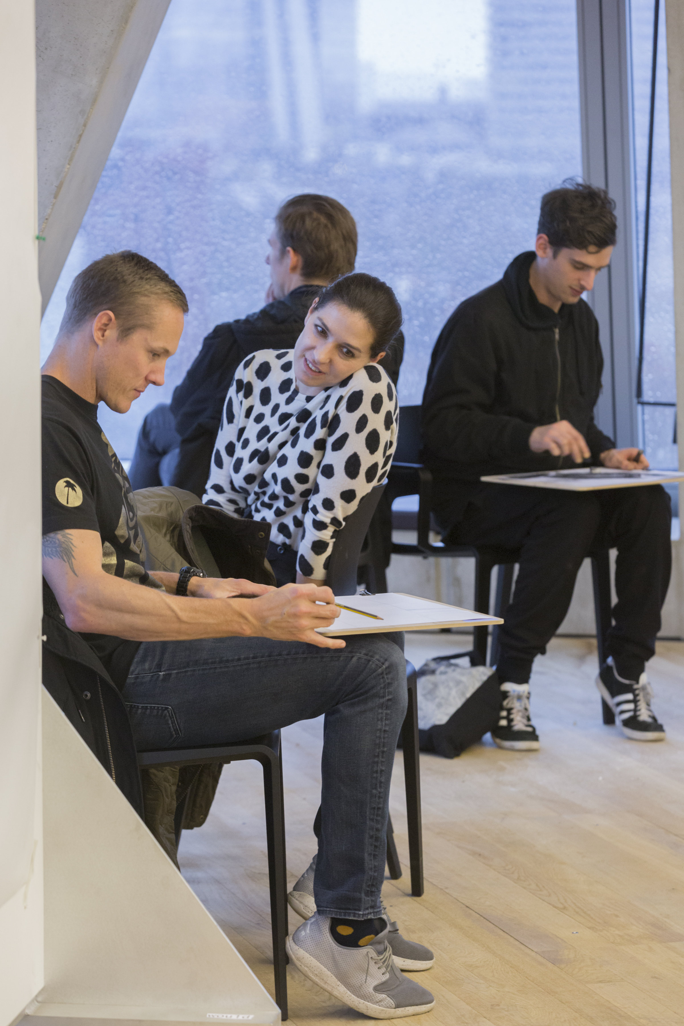 young people sit drawing in an art workshop