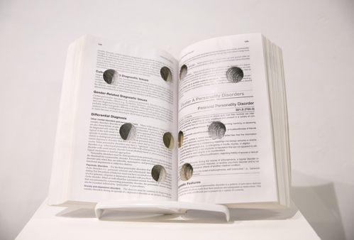 a book opened at its centre to reveal holes bored through it
