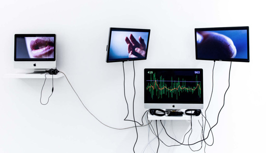 Image shows four computer screens against a white wall, two screens show close ups of mouth and hands and the others show the rate of the heart beat
