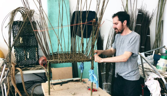 Artist Oliver willow weaving a sculpture