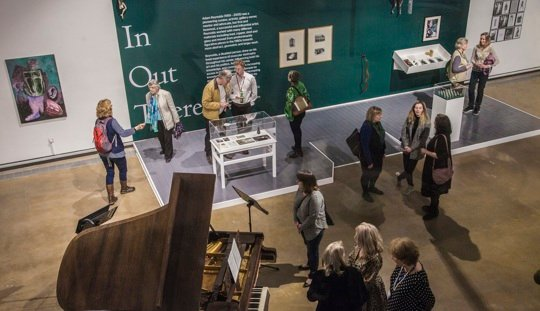 A gallery room with work on the walls and on plinths, viewed from above, with people standing around looking at the work and chatting