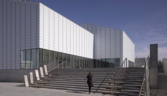 A white modernist gallery building set against a blue sky