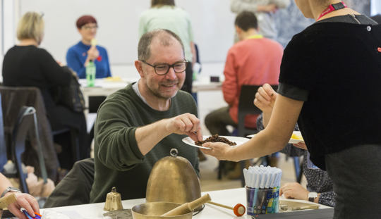 man leans forward whilst involved in a workshop; the man is surrounded by other people, all of whom are using art materials in an atmosphere of enjoyable activity