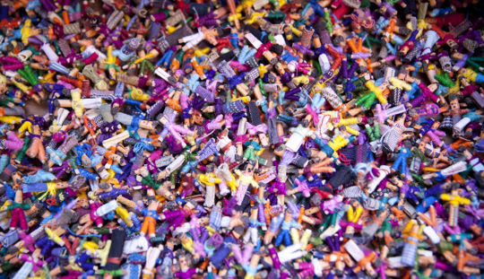 Close-up of a heap of tiny, colourful worry dolls