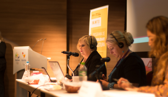 Three women leading a training conference.