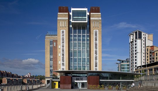 Baltic Centre for Contemporary Art. Tall brick building with large glass windows in front of a bright blue sky.