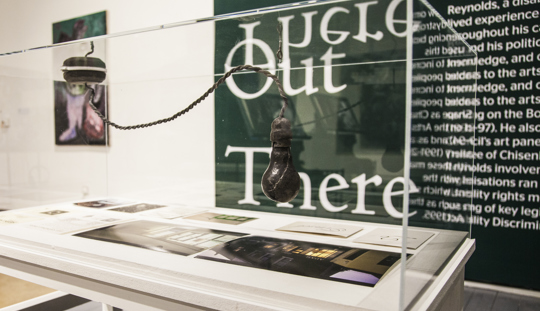 A lightbulb on a wire, both made of lead, hanging in a long rectangular vitrine on a plinth in a gallery space. The words out there can be seen on the wall behind