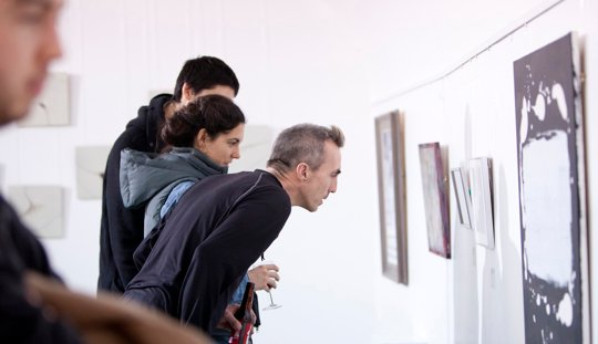 Three people observing an artwork