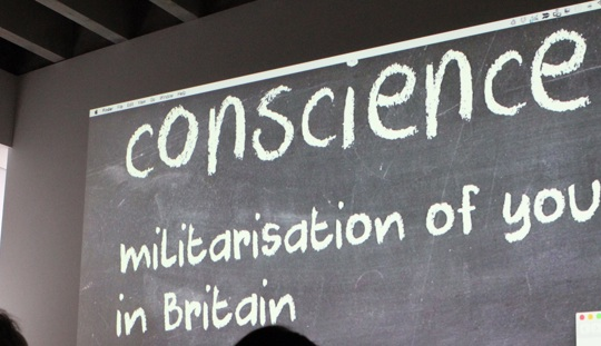 The words, Conscience: militarisation of British youth written on a blackboard in a darkened discussion room