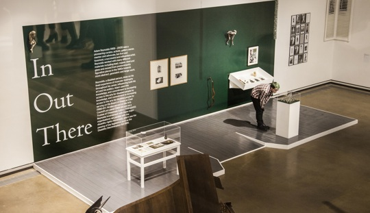 View from a high perspective of a large gallery room with sculptures on plinths, vitrines, framed items on the walls and In Out There in large text on the wall