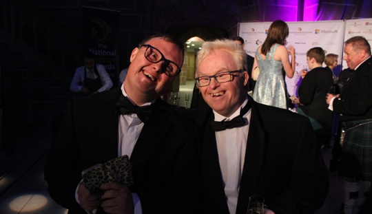 Artists Danny Smith (left) and Richard Hunt (right), two white men wearing tuxedos, are stnaidng together smiling widely at a formal party