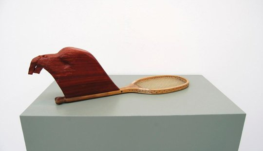 A plain wooden tennis racket with a dark orangey brown wooden sculpture that looks like a very stylised beavers head built on to the handle. The sculpture sits on a light grey plinth in front of a white background.