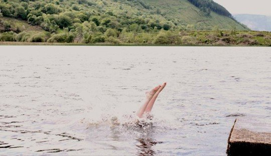 Image of a person diving into a huge lake, it looks like a Scottish loch. Just the feet are visible sticking out of the water.