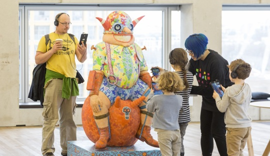 A group of adults and children, one of them wearing a Shape Arts tshirt, are standing in a gallery space around a life-size, brightly-coloured, cartoonish sculpture of a smiling man. They are smiling while looking at iPads which they are holding up t