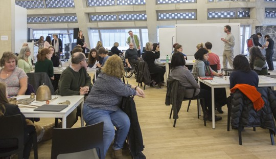 dozens of people seated in an artist workshop, with artist materials, easels and sketches on a large blackboard suggesting much activity is taking place whilst the participants, of mixed ages and background, appear to be waiting for the next instruct