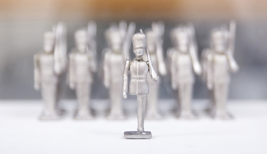 Close-up image of a row of small tin soldiers standing on a white plinth. The soldier at the front - the steadfast tin soldier - has one leg.