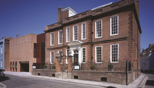 Image of a large, red-brick Georgian house on a road with buildings either side and a bright blue sky behind