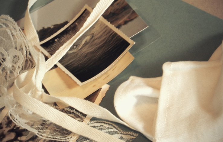 Old photos, ribbons and lace lay on top of an archival folder