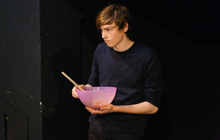 Teenage boy holding a mixing bowl and staring away from the camera