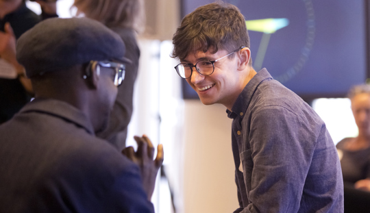James sits down, he has glasses and a navy shirt on, hes talking and smiling with an artist whos back is to the camera, the Unlimited Artist Welcome Day is out of focus in the background at Southbank Centre