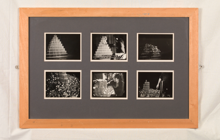 Six small-sized black and white photographs of  a sculpture made from  chairty collection boxes in a wooden frame hanging on a white wall