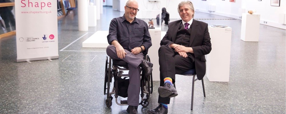 Two middle-aged white men sit next to each other smiling facing the camera. The man on the left is sitting in a wheelchair; the man on the right is wearing a suit. They are in a very large white-walled gallery space filled with contemporary art and a
