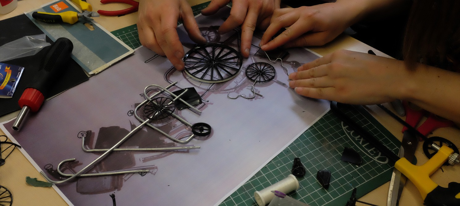 Two pairs of hands touching a miniature wheels  next to a bunch of tools