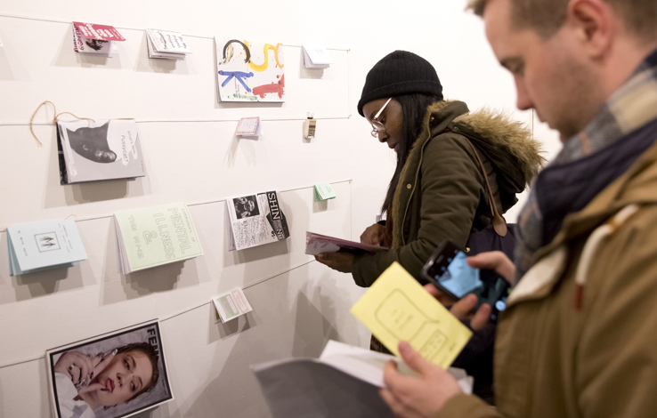 people stand at wall reading zines on string