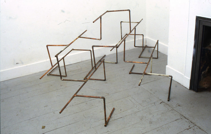 A large, geometric sculpture of narrow copper pipes on a sitting on a grey painted gallery floor with white walls background