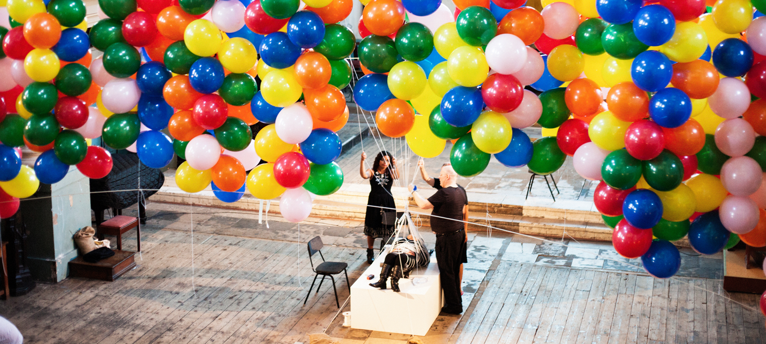 Image taken from ceiling perspective. Hundreds of multicolour baloons hang above a figure laying on a white plinth