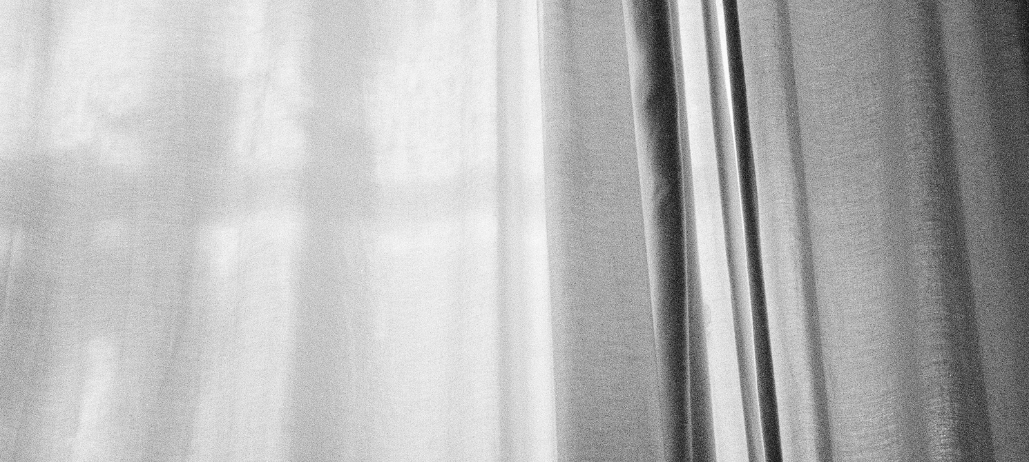 grainy black and white photo shows a sheer curtain with shadows underneath it, and a heavier curtain to the right of the photo, the point of view is looking up and the section of the curtain takes up the full frame