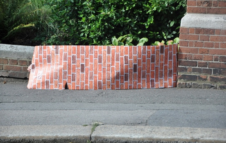 a corner of a road shows a brick wall, with a large printed paper brick covering part of the wall