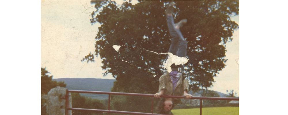 An archived photograph of Tony Heaton balancing upside down on a fence.