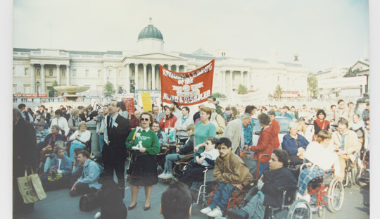 An old photograph of a crowd of protesters gathered for a rally in Londons Trafalgar Square. Many of the protesters are wheelchair users.