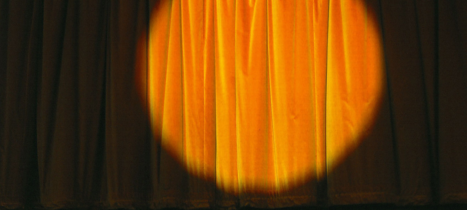 a spotlight shines on a stage curtain on an empty stage