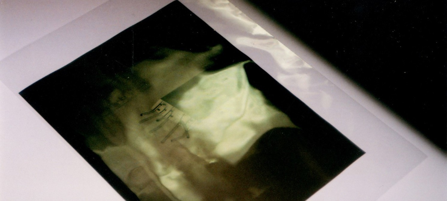 A dark, blurry photograph in a plastic folder on a white table in a dark room. It is hard to make out what the photograph is of.