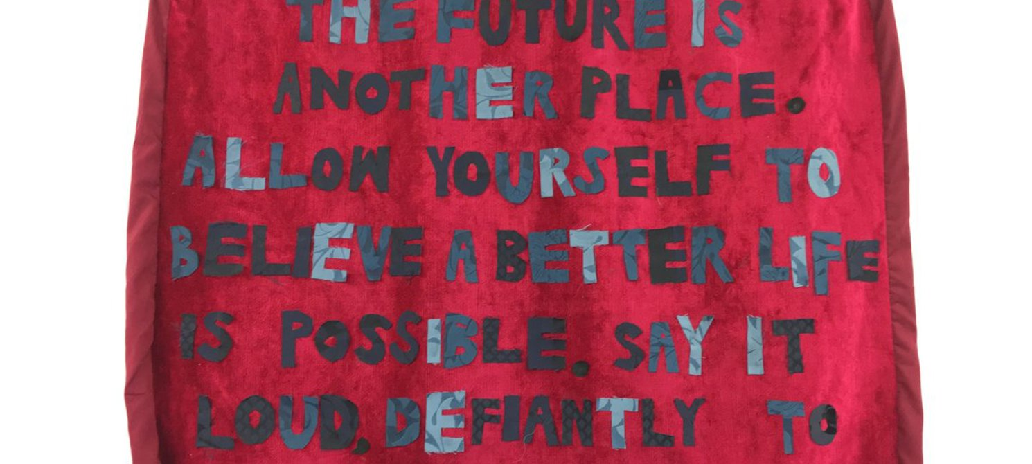 A textile piece photographed as it hangs on a white wall. Upon a rich red backdrop of velvet fabric, with a rough hem around the edges, are appliqued words. The bold, capital letters are made from fabric in varying shades of grey. They have a hand-cu