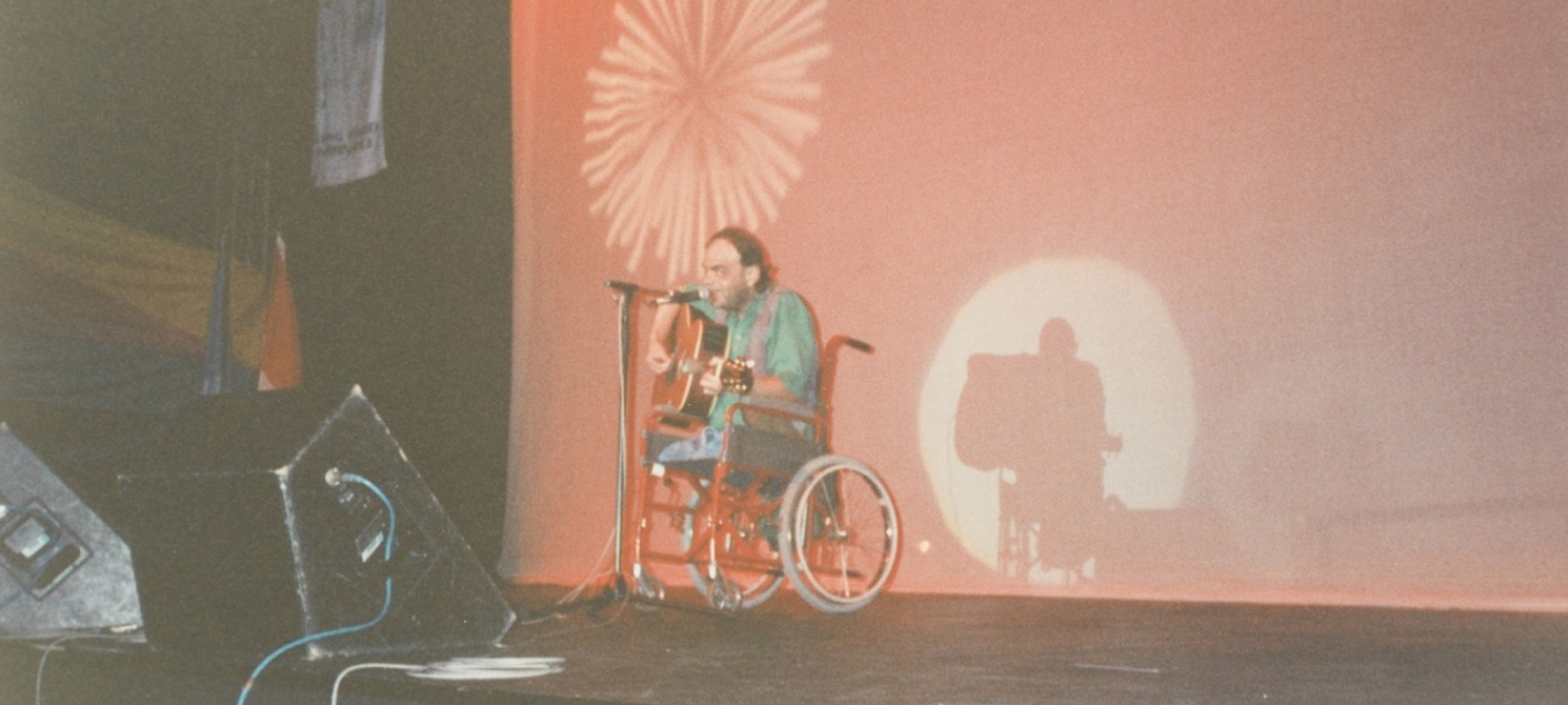 A man is using a wheelchair, playing guitar and singing on stage