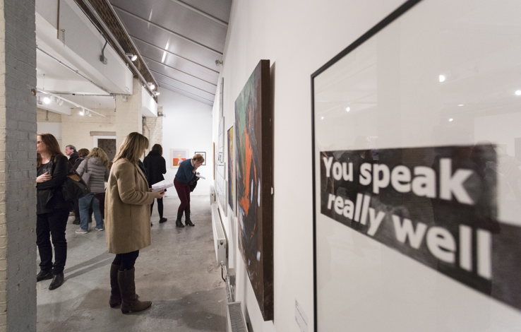 In the foreground to the right is an image that reads you speak really well with other exhibits and vistors looking in the background out of focus