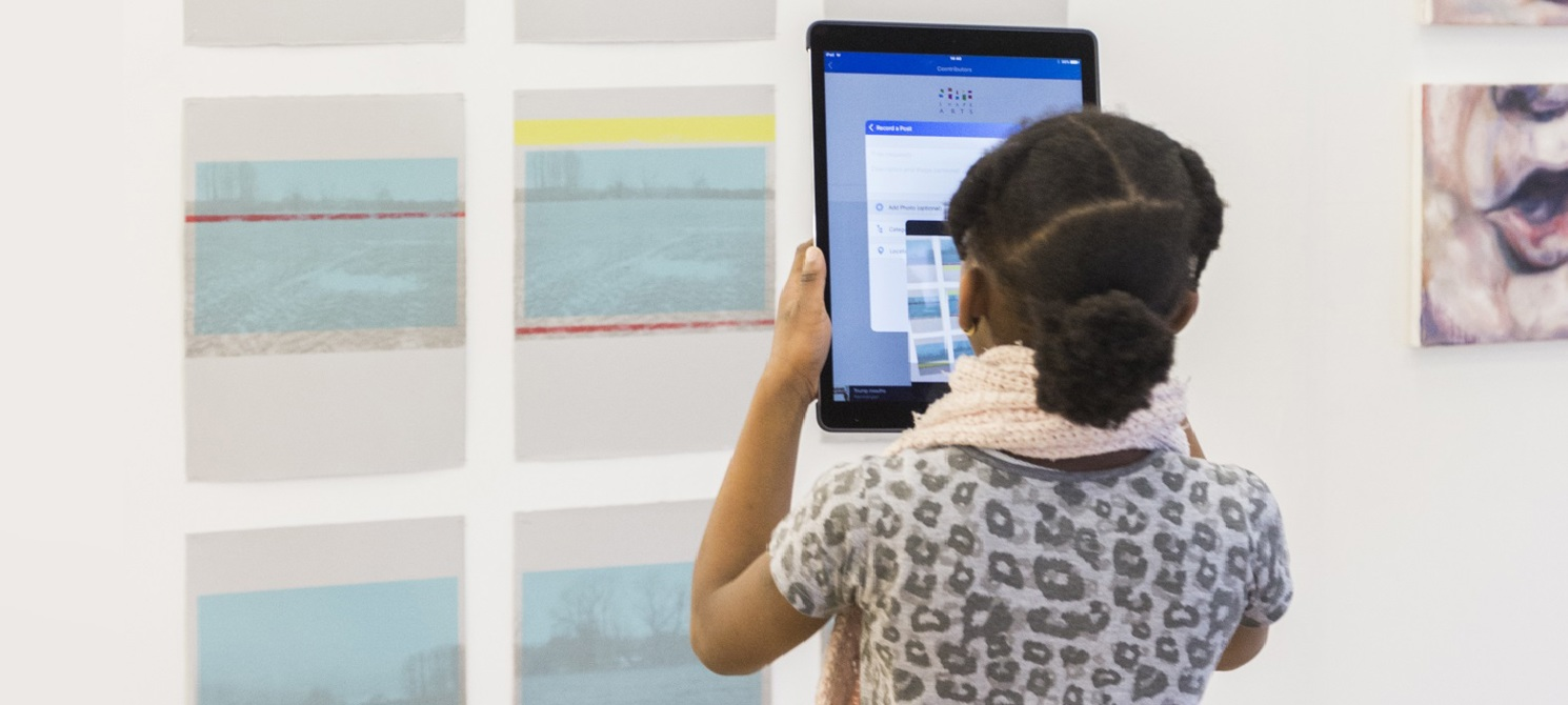 A young girl in a dress is standing in a gallery looking at some pieces of art on paper pinned to a wall. She is holding up an iPad, pointed at the art.