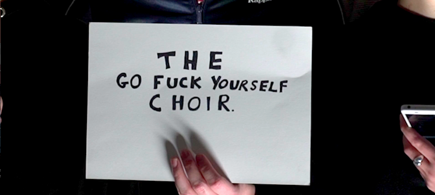 A white hand holds up an A4 sheet of paper, on which the text The Go Fuck Yourself Choir is handwritten in capital letters.