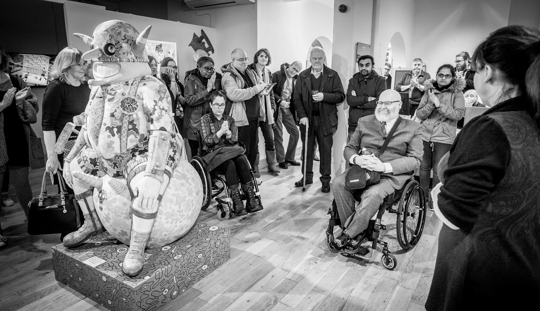 Jason in his wheelchair behind his Billy Boy work, surrounded by an applauding audience. Image is black and white and has a sense of pride about it.