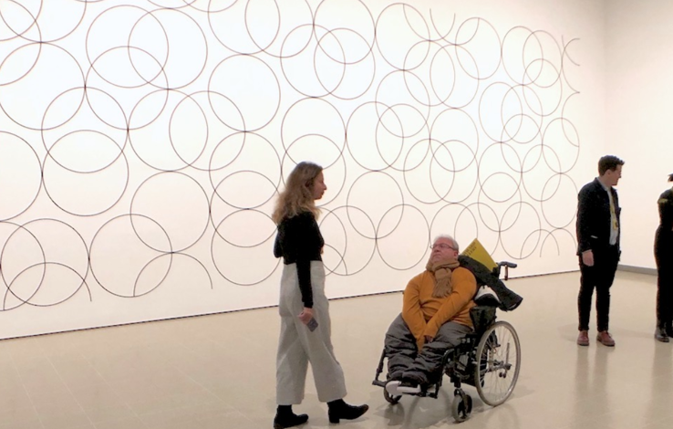 Image shows David in a gallery space speaking with a young girl in grey trousers with blond hair. David is wearing a mustard jumper. There are two other visitors in the background.